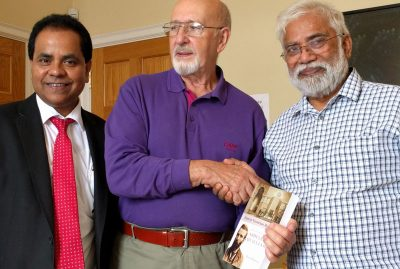 Mumin and Galib presenting Brian with Ron's book